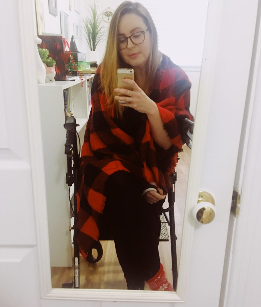 Lisa is sitting on her black collator in front of a mirror in a white room. She is wearing a red and black plaid blanket scarf, black leggings and red socks with a black cast on her arm. Her legs are crossed. Her hair is straightened and she's wearing glasses.