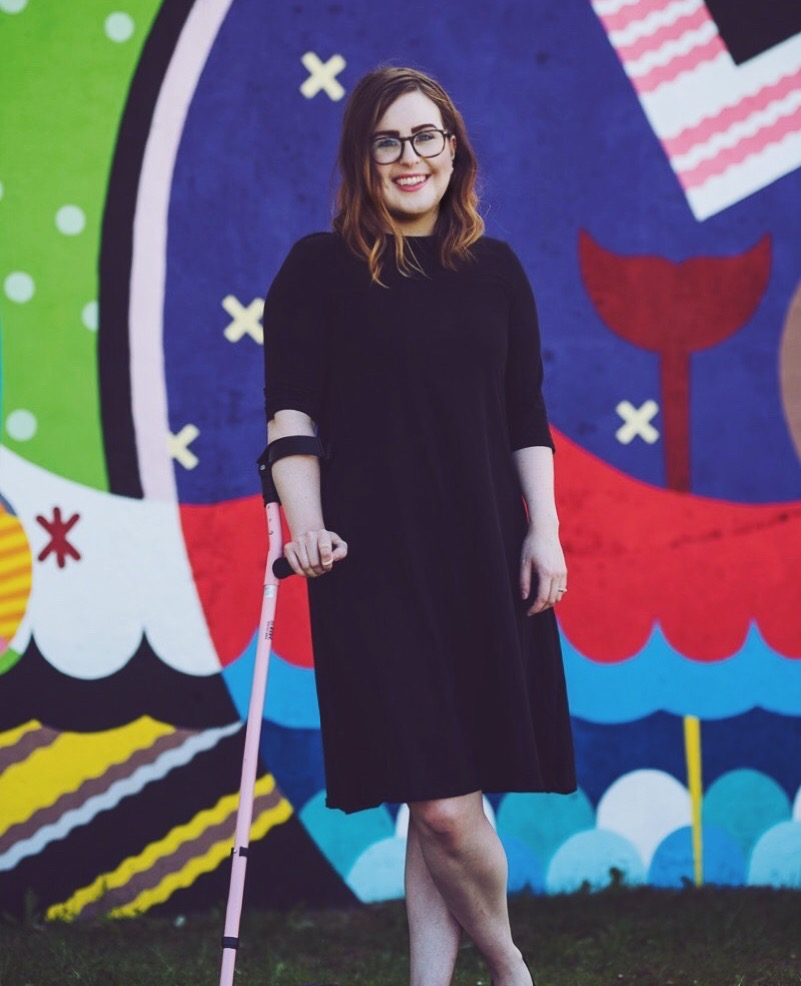 Lisa is wearing a black knee-length dress and holding her pink crutch. She is standing with one leg crossed in front of the other, in front of a very colourful mural.