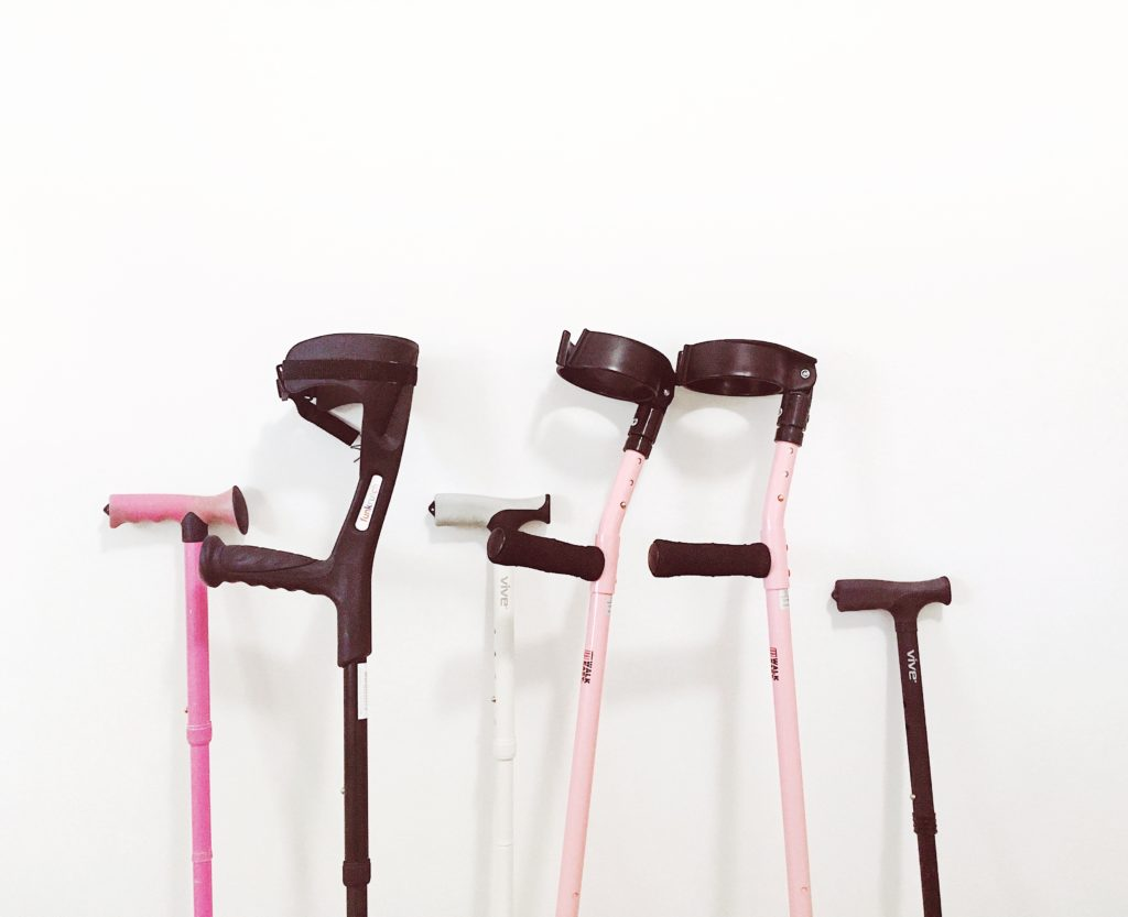 There are 6 canes and crutches lined up against a white wall. Starting from the left there is a pink cane, black cutch, white cane, two pink crutches, and a black cane.
