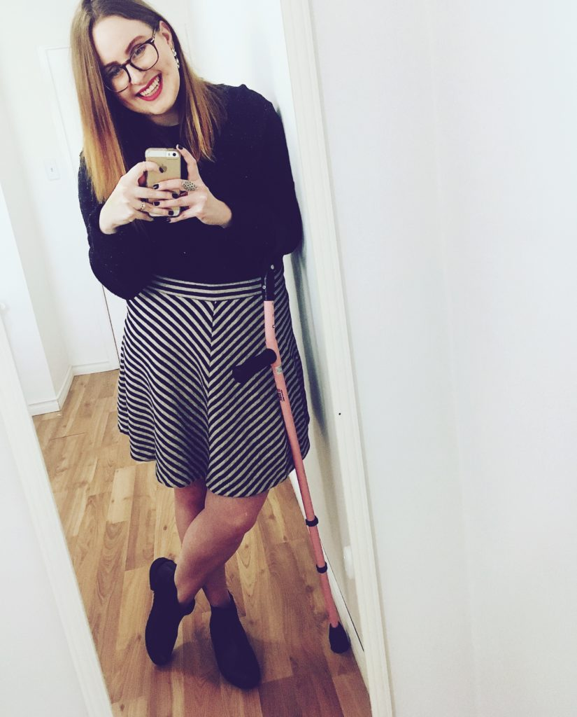 Lisa is facing a mirror in a white room. She is holding her phone and has her pink crutch hanging from her arm. She is wearing a black sweater, black and white striped knee-length skirt and black ankle boots.