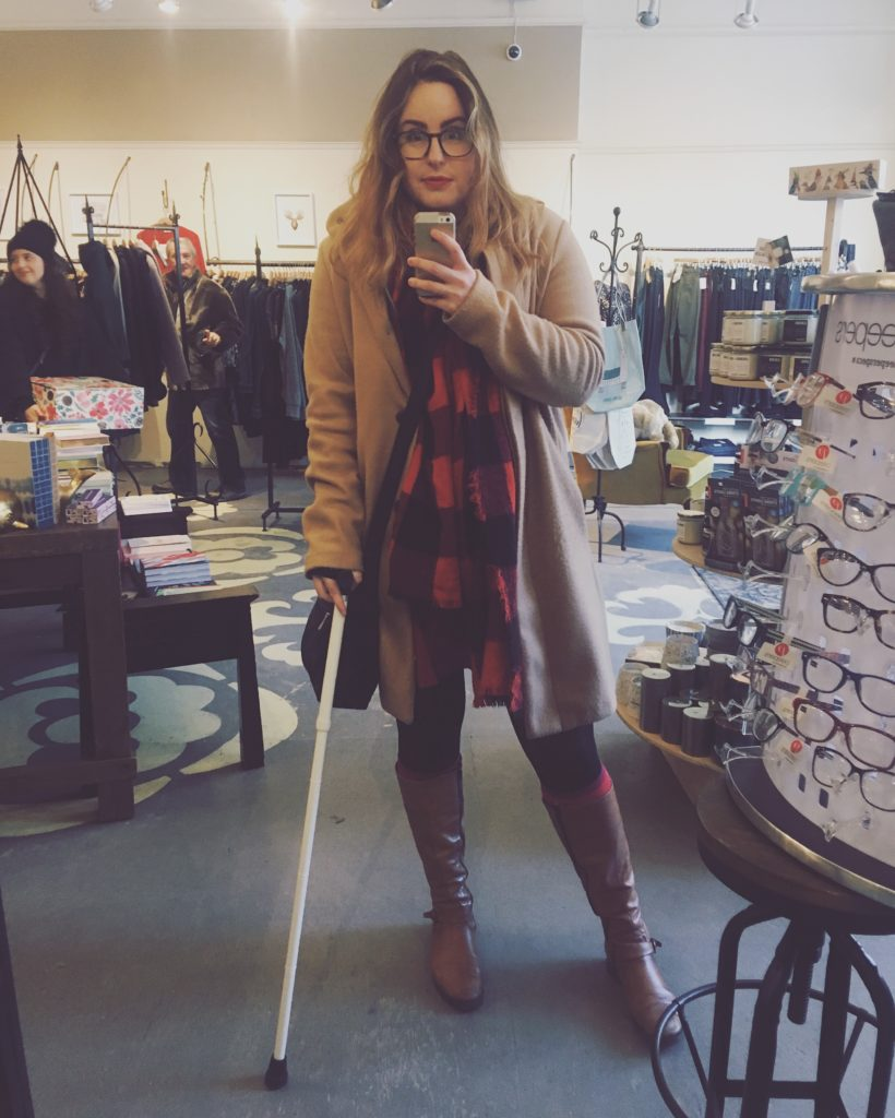 Lisa is standing in front of a mirror in a clothing store. Her hair is curly, and she is wearing a beige pea coat, red and black plaid scarf, black tights, brown knee high boots, and is holding a white cane.