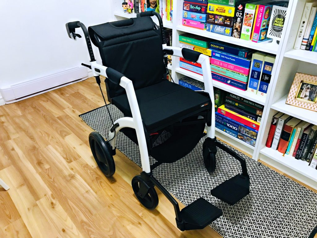 This is an image of Lisa's white and black Rollz Motion in it's third position, the wheelchair. It is placed on a black and white rug in front of Lisa's white bookcase with colourful books and puzzles.