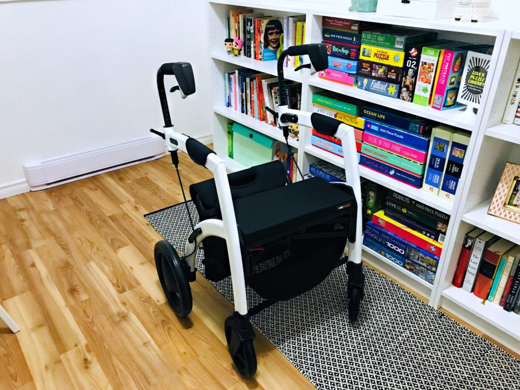 This is an image of Lisa's Rollz Motion in it's second position, a rollator with the chair bag attached. It is placed on top of a black and white rug in front of Lisa's white bookcase with colourful books and puzzles.