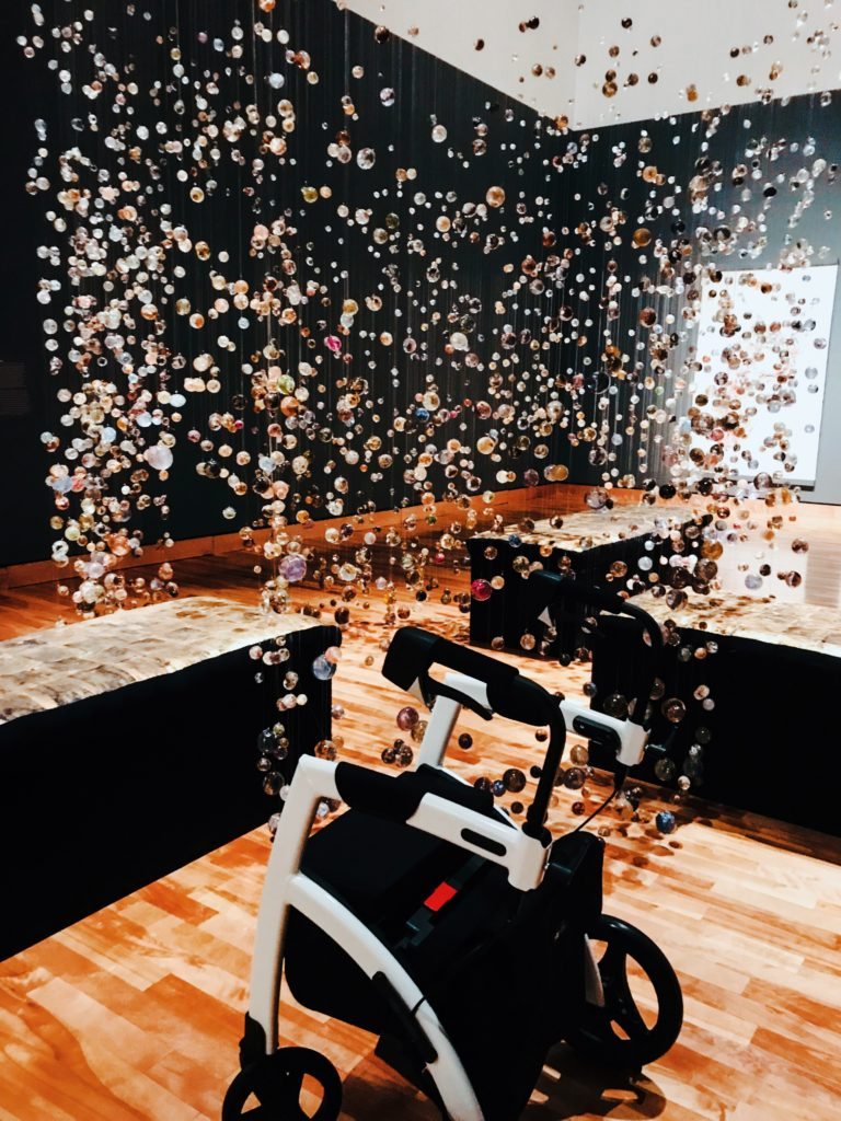 This is an image of Lisa's white and black Rollz Motion rollator in position in front of an art exhibit at a museum. There are thousands of tiny, colourful glass orbs hanging from the ceiling.