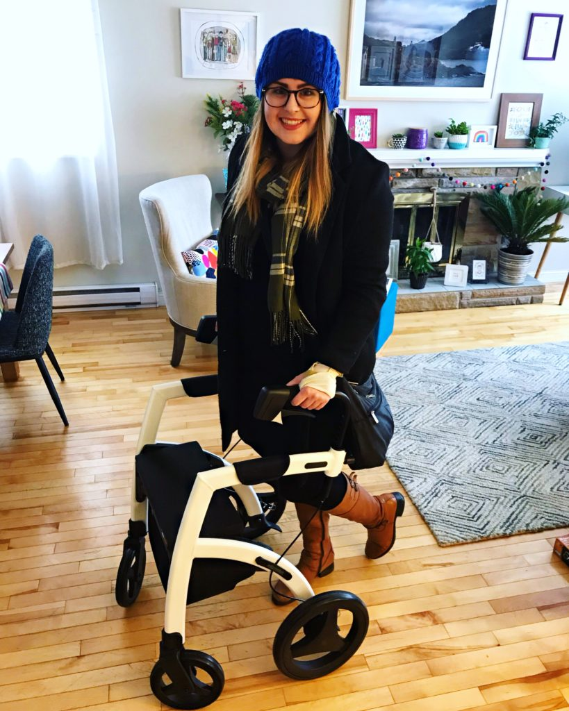 Lisa is standing behind her white and black Rollz Motion rollator in her living room. She is dressed in a blue winter hat, a black coat, a plaid scarf, black pants, and brown knee-high boots. She is smiling into the camera.