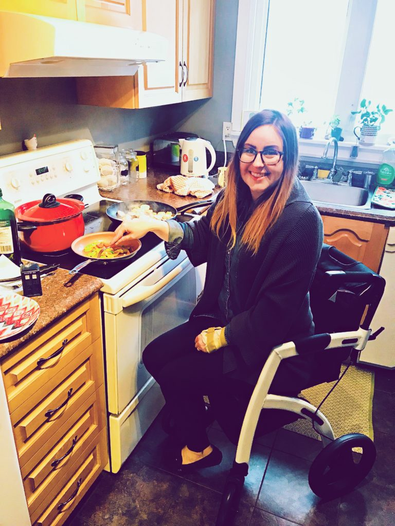Lisa is sitting on her Rollz Motion chair next to the oven in her kitchen. She is flipping peppers in a pan and smiling up at the camera.