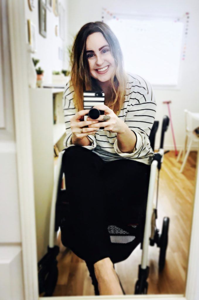Lisa is sitting in her white and black Rollz Motion wheelchair. She is smiling into the camera. She is wearing a white and black striped shirt, black pants, and black heels. Her phone is in her hand.