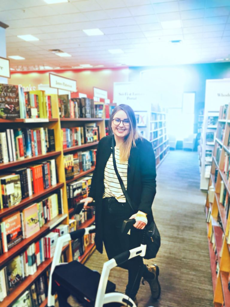 Lisa is standing behind her white and black Rollz Motion rollator in a bookstore. She is smiling at the camera. She is wearing a black jacket, a white and black striped shirt, jeans, and bloodstones. She is leaning on her rollator.