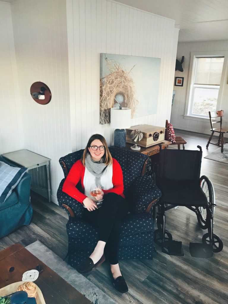 A photo of me sitting in a chair in the living room at Blueberry Cottage. There is a glass of wine in my hand and my wheelchair is next to the chair.