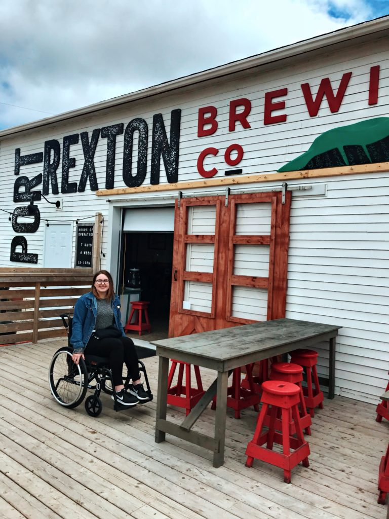 A photo of Lisa sitting in her wheelchair on a deck in front of a white building with a large sign on it that reads Port Rexton Brewing Co.