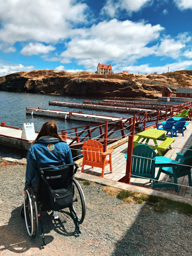 A photo of Lisa in her wheelchair looking out at the ocean in Trinity. There are colourful deck chairs around and a house on a cliff in the distance. Lisa is back on to the camera.