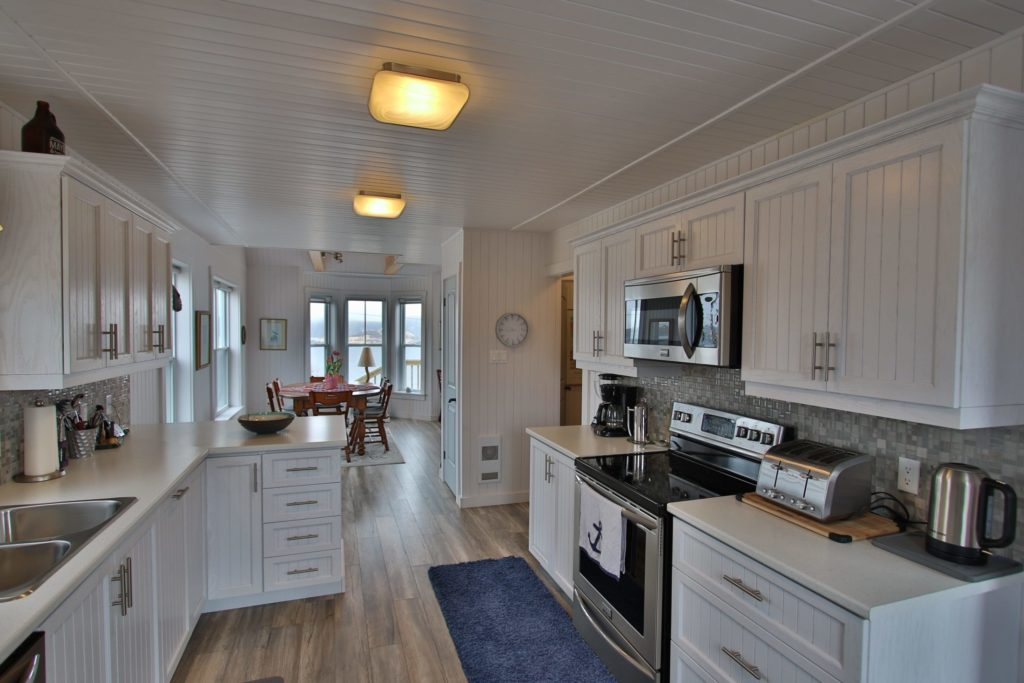 A photo of the kitchen at Blueberry Cottage. White cupboards and walls with stainless steel appliances opening into a dining room with panoramic windows.