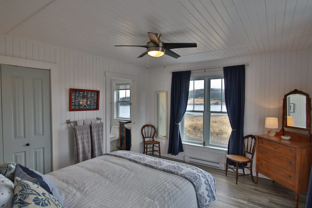 A photo of the main floor queen suite at Blueberry Cottage. White walls with a queen bed facing a large window with navy curtains. On either side of the window are two wooden chairs.