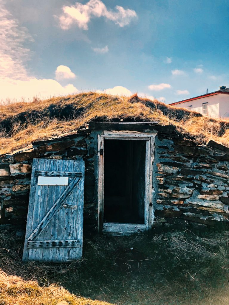A photo of a root cellar. There is a small door built into a hill and you can see that it goes underground.