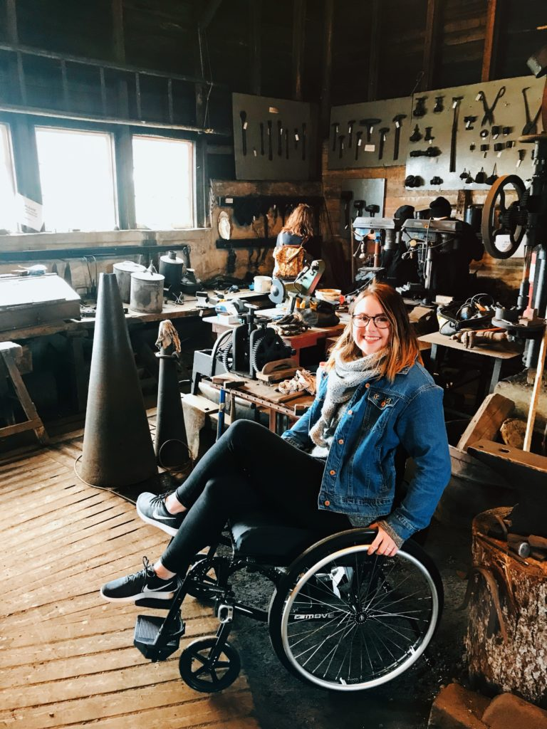A photo of me in my wheelchair inside Green Family Forge. All around me are blacksmith tools and supplies.