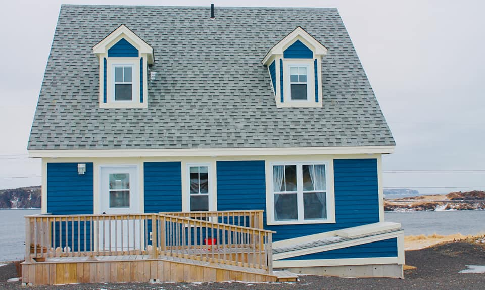 A photo of the exterior of Blueberry Cottage - a dark blue house A frame house with white trim.