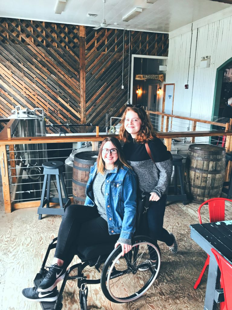 A photo of Lisa and Pamela inside Port Rexton Brewery. Pamela is standing behind Lisa's wheelchair and they are smiling at the camera.