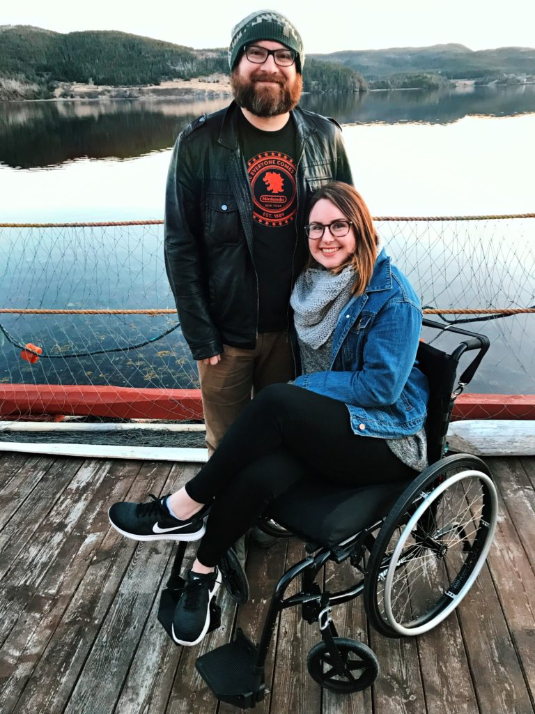 A photo of Lisa and Matthew on the dock behind the Twine Loft. Lisa is sitting in her wheelchair and Matthew is standing up beside her. Behind them is the water.