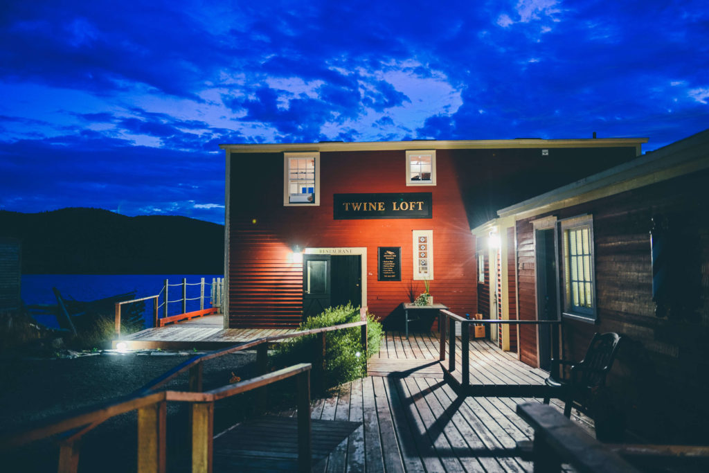 A photo of the exterior of the Twine Loft restaurant at night. It's a red fishing stage with a dock next to the water.