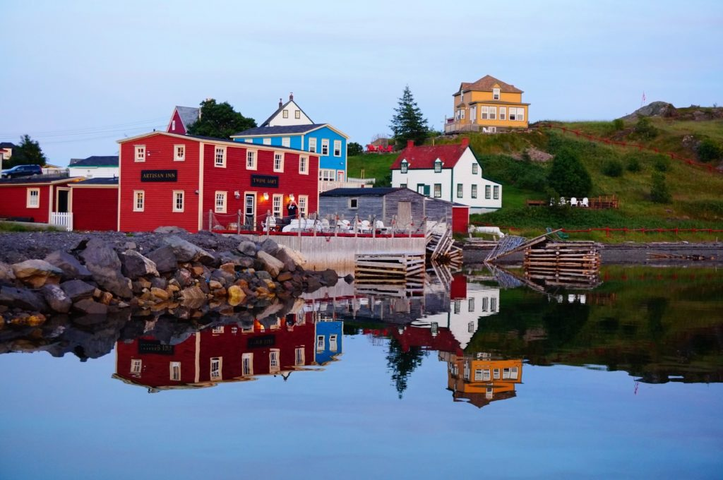 A picture of Trinity, Newfoundland. In the forefront is a body of water, then a dock and colourful salt box homes nestled throughout some hills.