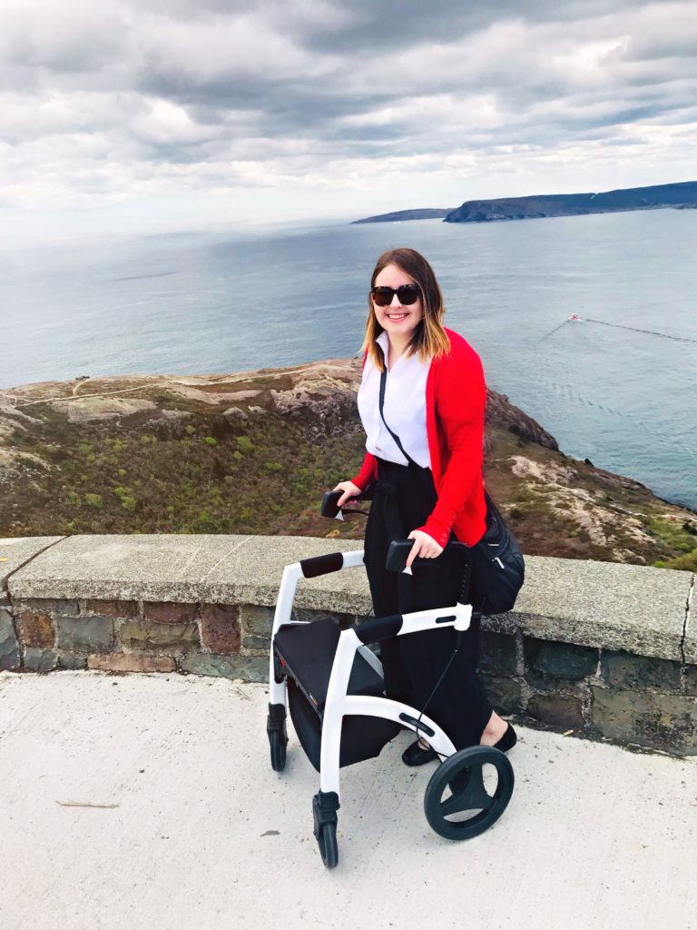 A photo of Lisa on top of Signal Hill with her white and black rollator. She is wearing a red cardigan, white blouse and black pants. Behind her is a cliff, the ocean, and a walking trail that has 7 million trillion stairs.
