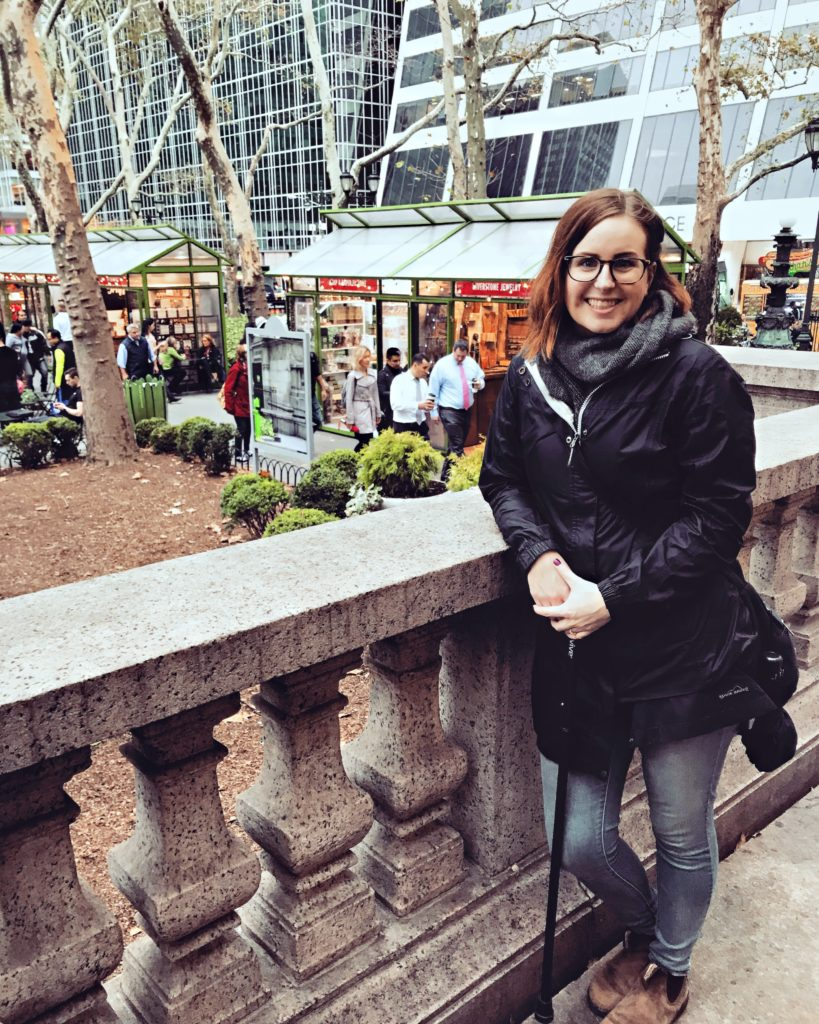 A photo of Lisa leaning against a railing in Bryant Park in New York City. She's wearing a black coat and jeans, and is holding a black cane in her hand. She is smiling because she is on her honeymoon and having a blast.