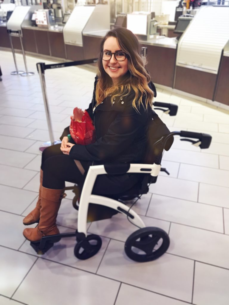 A photo of Lisa sitting in the transformed wheelchair version of her Rollz Motion rollator. She's wearing all black with brown boots, is holding a bag of popcorn and is smiling at the camera even though she isn't allowed to eat the popcorn.