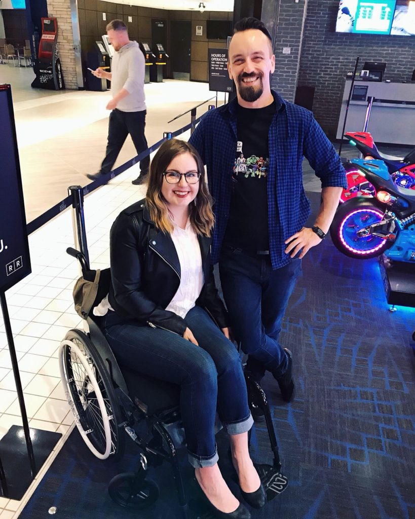 A photo of Lisa sitting in her wheelchair at The Rec Room. Standing next to her is her friend Jonny, a non-disabled person who miraculously doesn't think its weird that disabled people need to use different mobility aids and doesn't ask disabled strangers intrusive questions about their health.