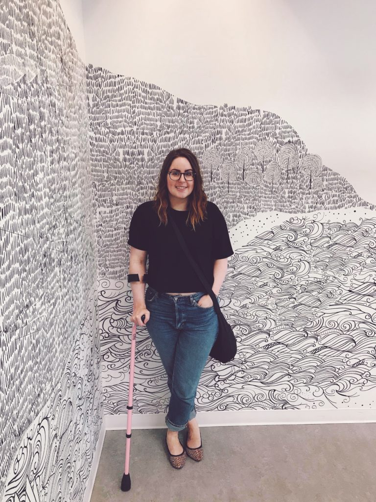 A photo of Lisa standing in front of a white wall with black text art. She is wearing a black t-shirt, jeans, and colourful flats. She is leaning on her pink crutch. She is smiling because she is at her favourite place in the world, Ikea.