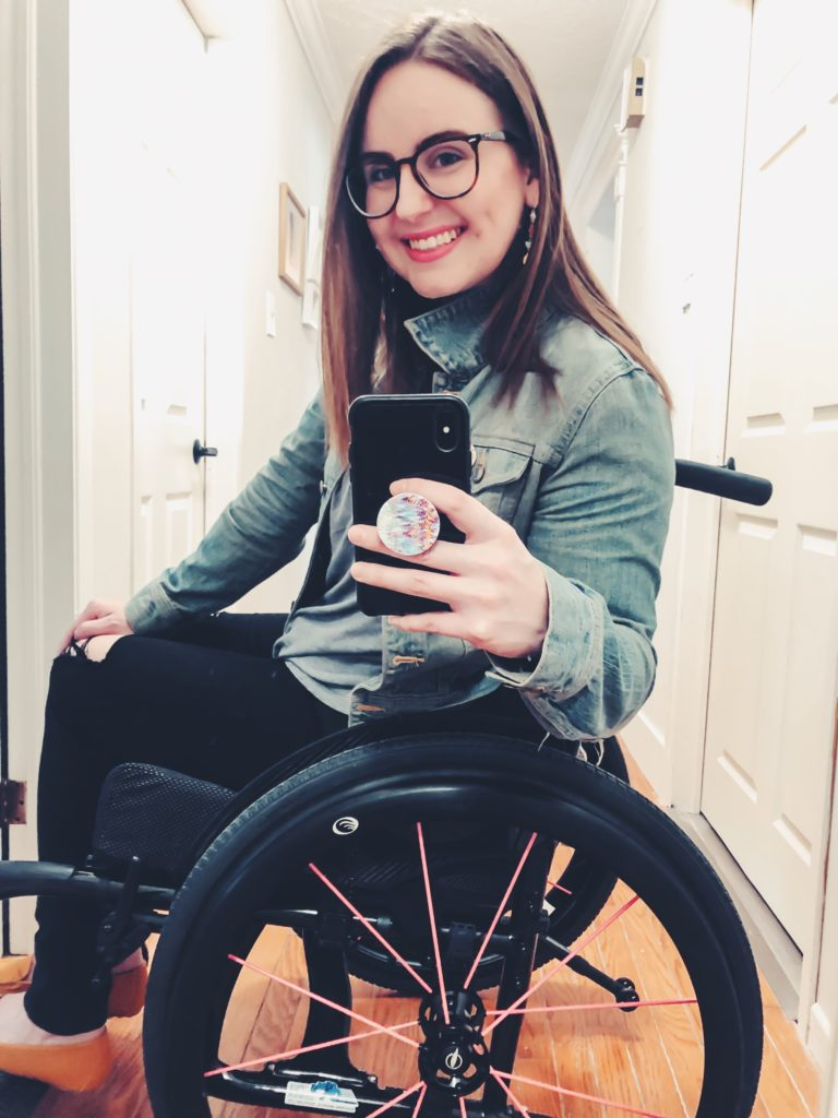 A mirror selfie of me turned side on while sitting in my new black wheelchair with pink spokes.