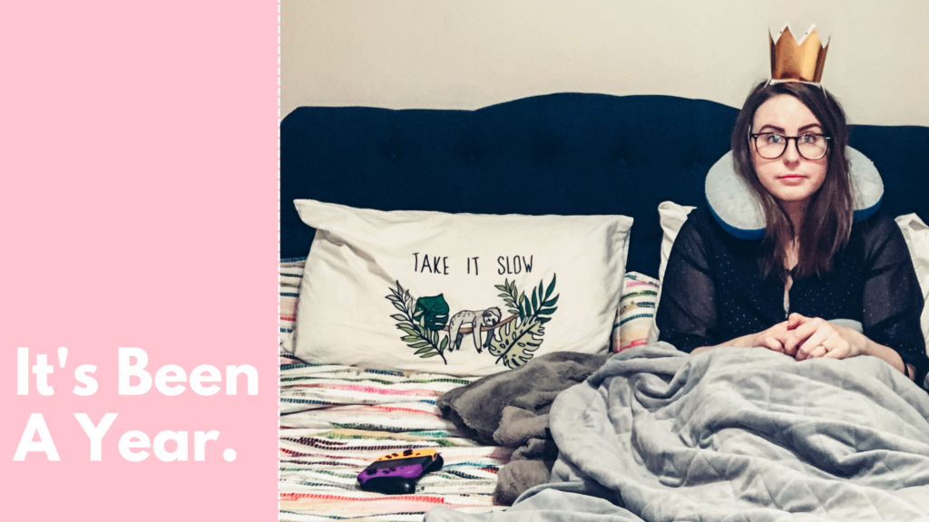"A blog banner with a picture of me sitting up in my bed wearing a black dress, a travel neck pillow, and a gold paper crown. Text reads ""It's been a year."""