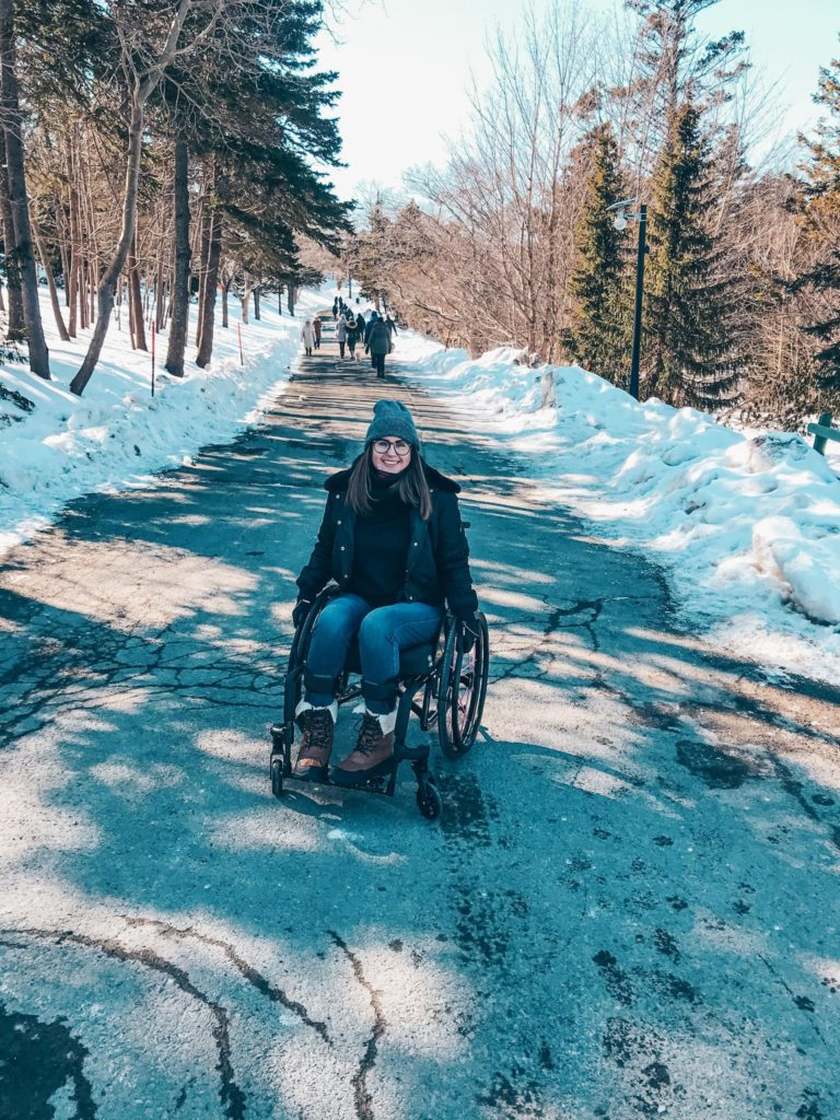 A photo of me dressed in my winter gear, sitting in my fancy new wheelchair on a paved trail in Bowring Park. I'm smiling because wheelchairs aren't sad.