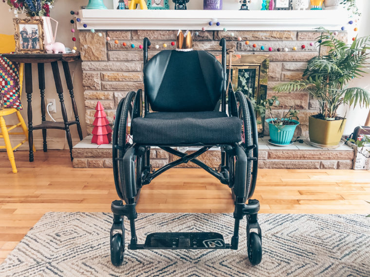 A photo of my black manual wheelchair in front of my fireplace that is filled with colourful decor. On the backrest of the chair is a small paper gold crown.