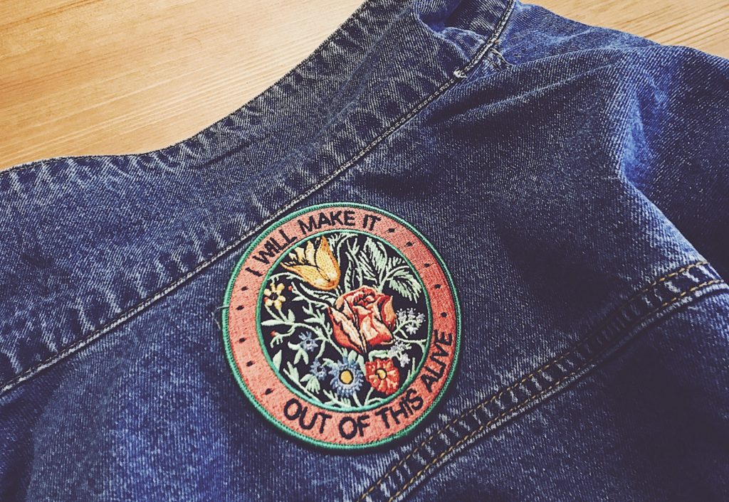 """A close-up photo of Lisa's jean jacket laying on top of a wooden table. In the top centre of the jacket is a large iron on patch with a lot of flowers that says """"I will make it out of this alive."""""""